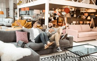 Cheerful laughing couple behaving childishly in furniture showroom