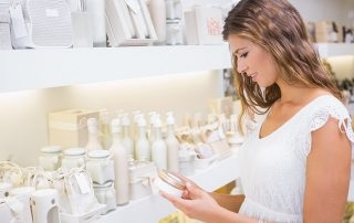 Smiling woman testing moisturizer