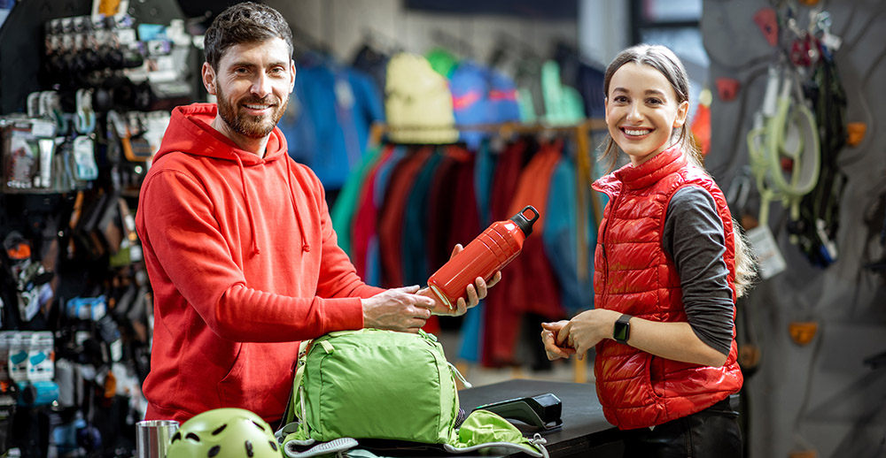 Woman with salesperson at the counter of sports shop create an emotional connection with your customers